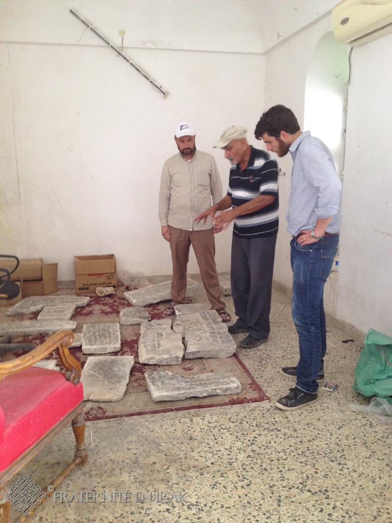 un garde-l'archéologue et guillaume devant les fragments de plaques retrouvées dans les gravas